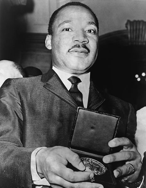 Martin Luther King, Jr. showing a medal given him.